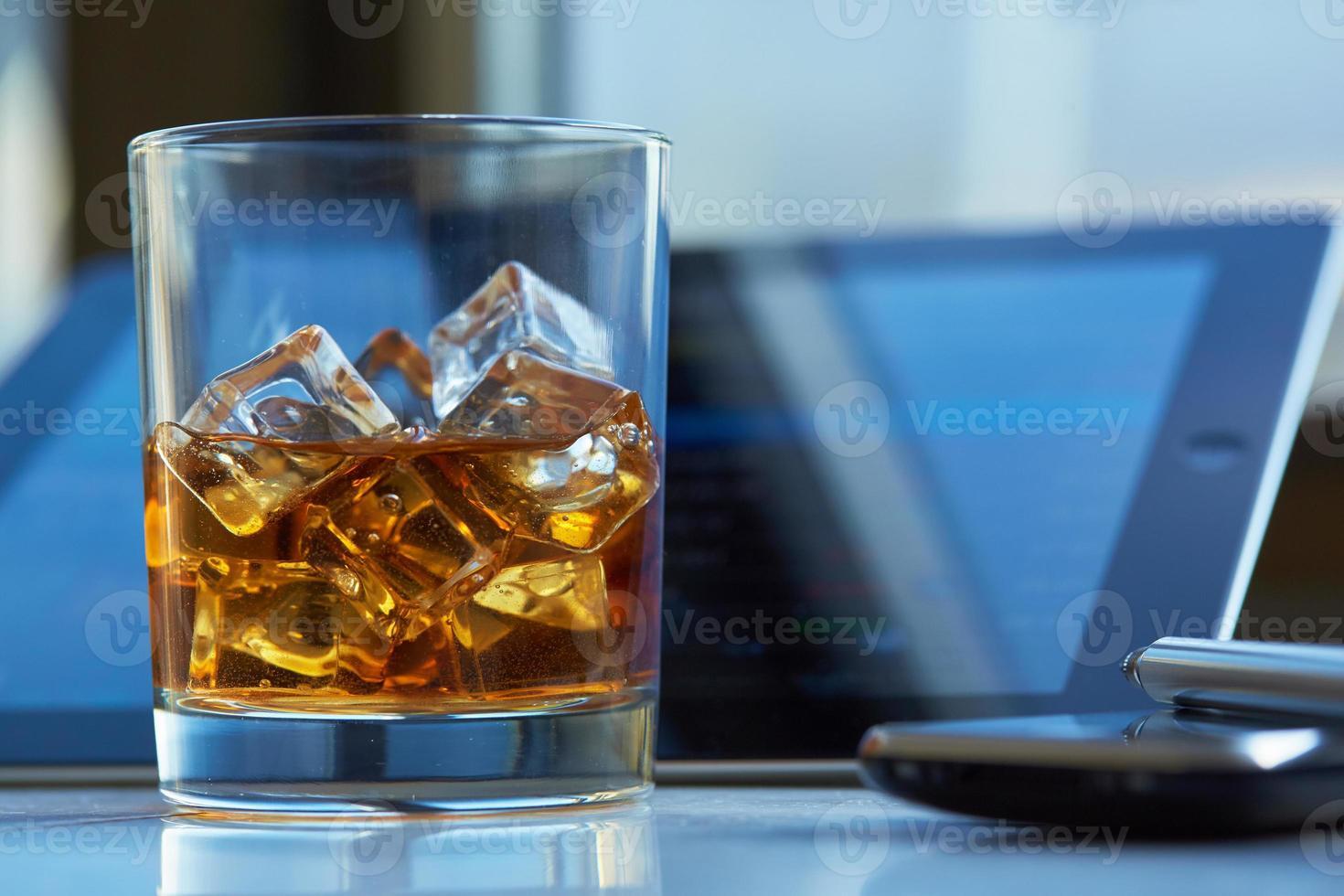 uísque com gelo, o tablet e o telefone em cima da mesa foto