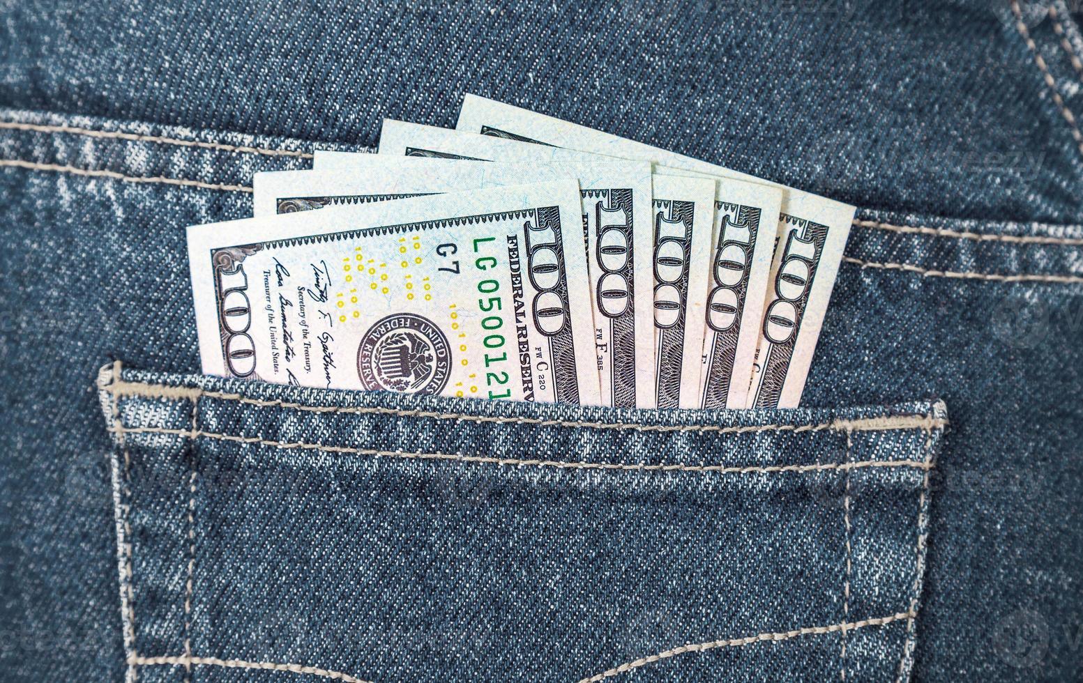 notas de dólares americanos no bolso de trás da calça jeans foto