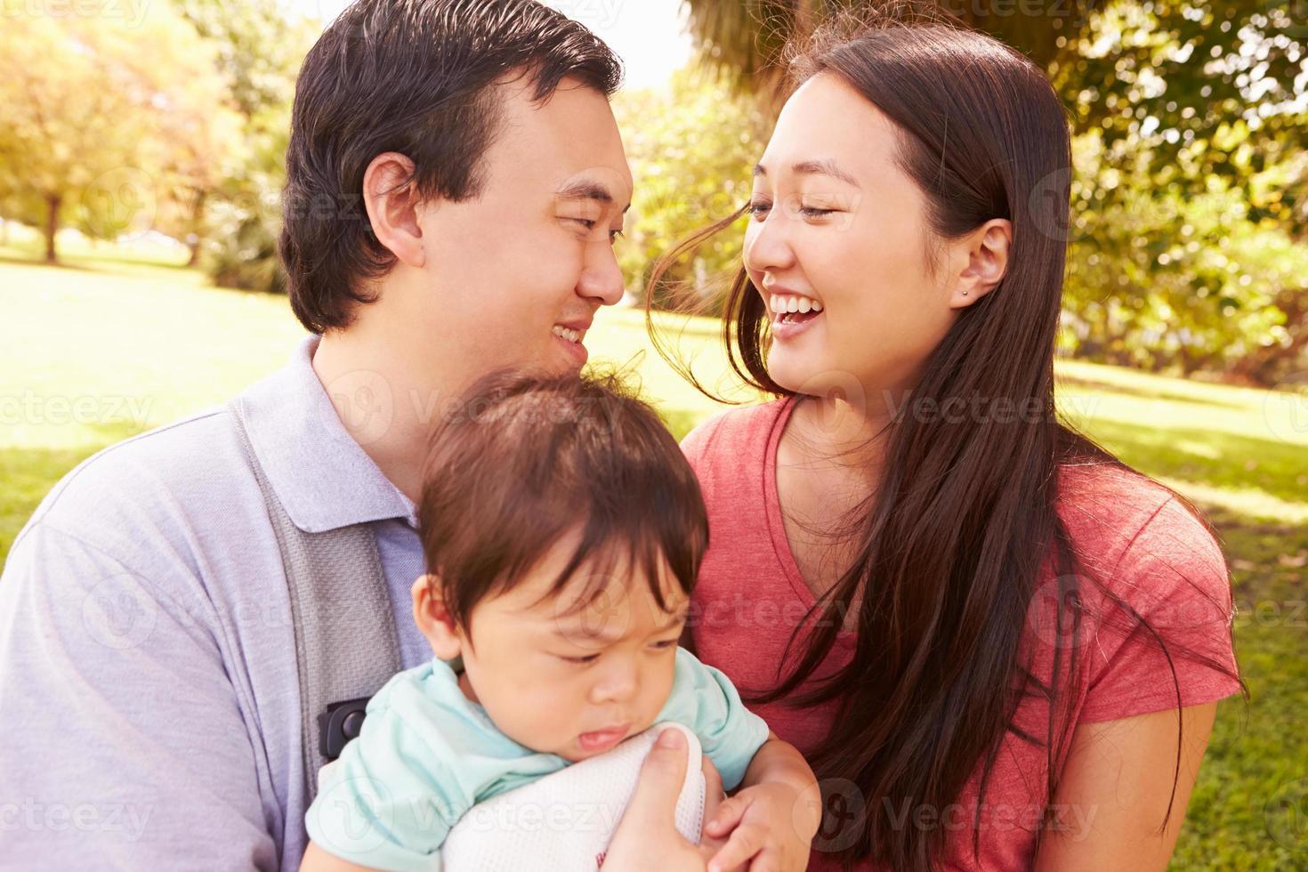 família com bebê em transportadora caminhando pelo parque foto