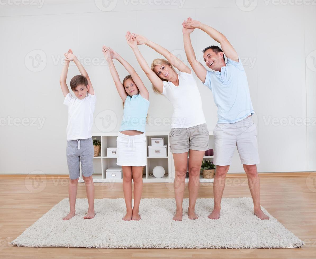 família fazendo exercícios de alongamento no tapete foto