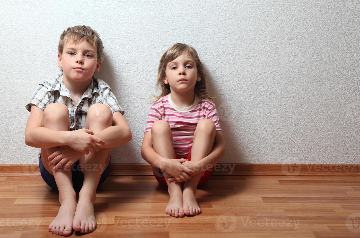 menina e menino pensativo sentar encostado na parede foto
