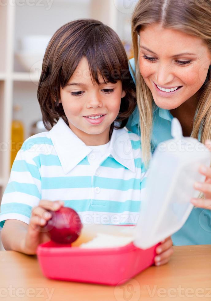 menino sorridente e sua mãe preparando o almoço escolar foto