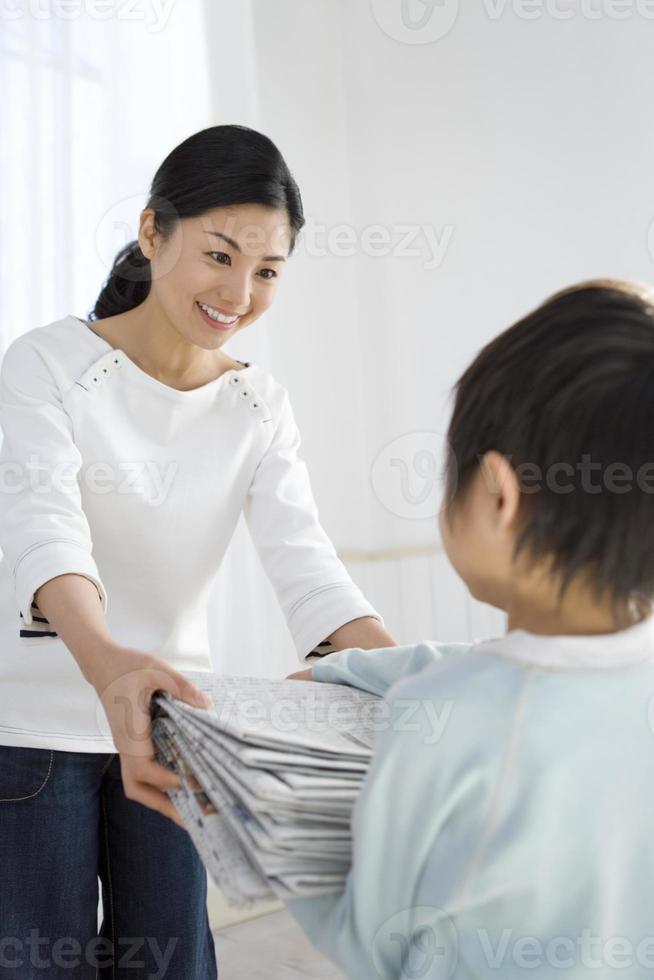 menino entregando mãe jornais velhos foto