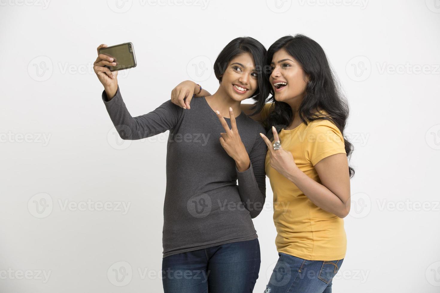 duas belas moças tomando selfie com telefone móvel foto