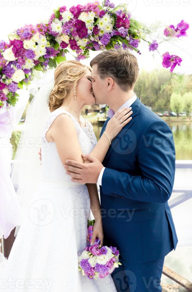 jovem noiva e noivo beijando sob arco na cerimônia de casamento foto