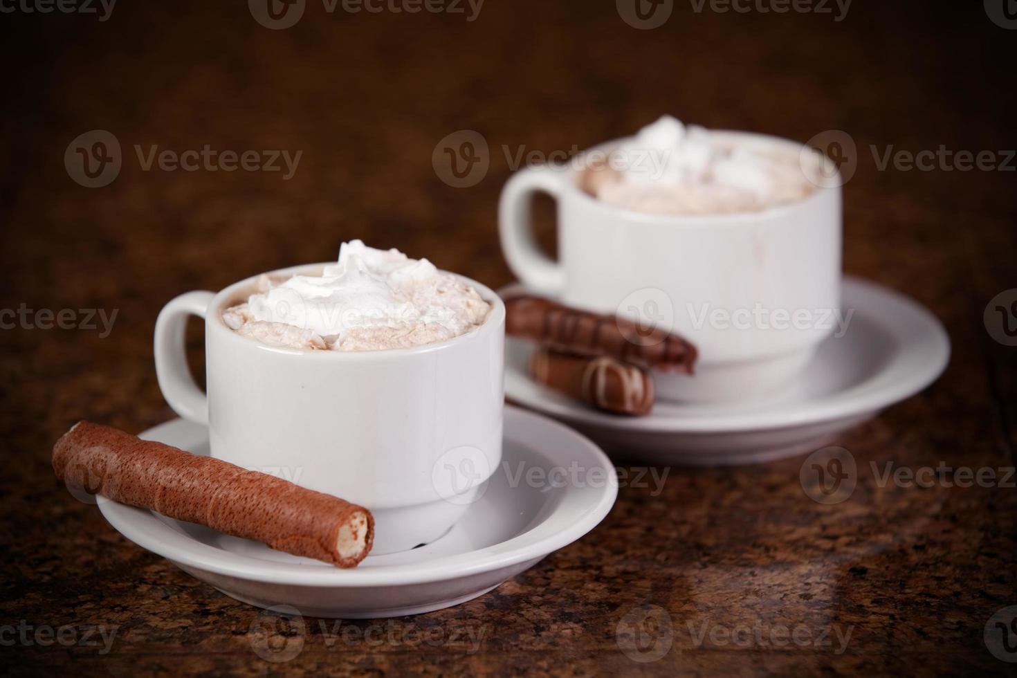 duas xícaras de café com chocolates e biscoitos foto