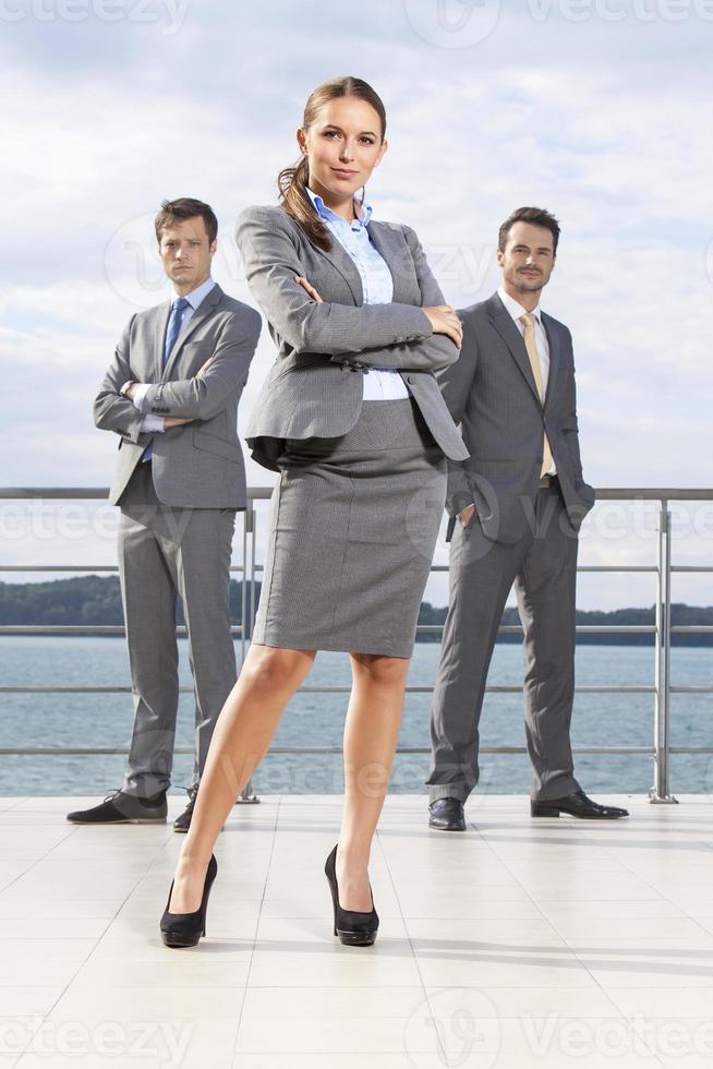 empresária confiante em pé com colegas de trabalho no terraço contra o céu foto