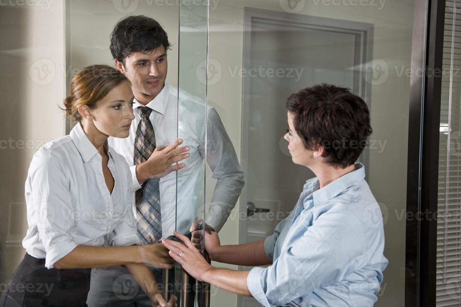 três trabalhadores de escritório na porta da sala de reuniões foto