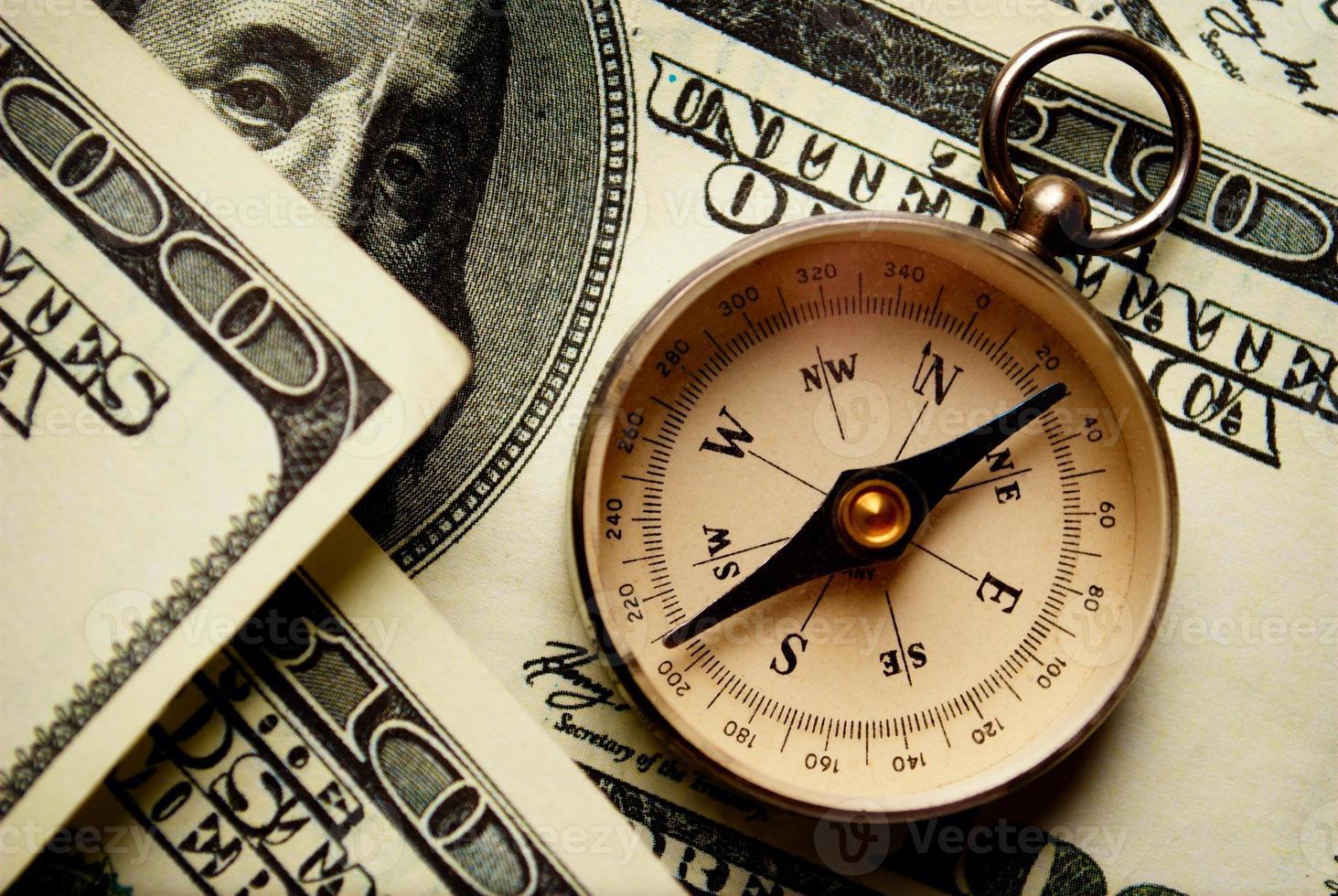 bússola magnética em notas de dólar foto