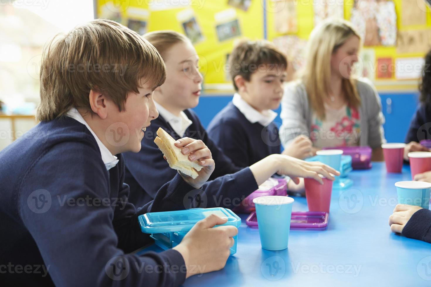 crianças em idade escolar com o professor sentado à mesa a almoçar foto