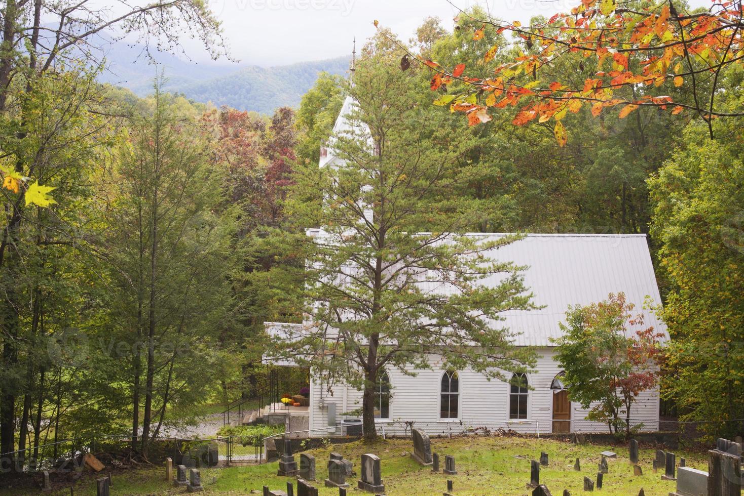 pequena igreja branca rondava com as cores do outono nos esfumaçados. foto