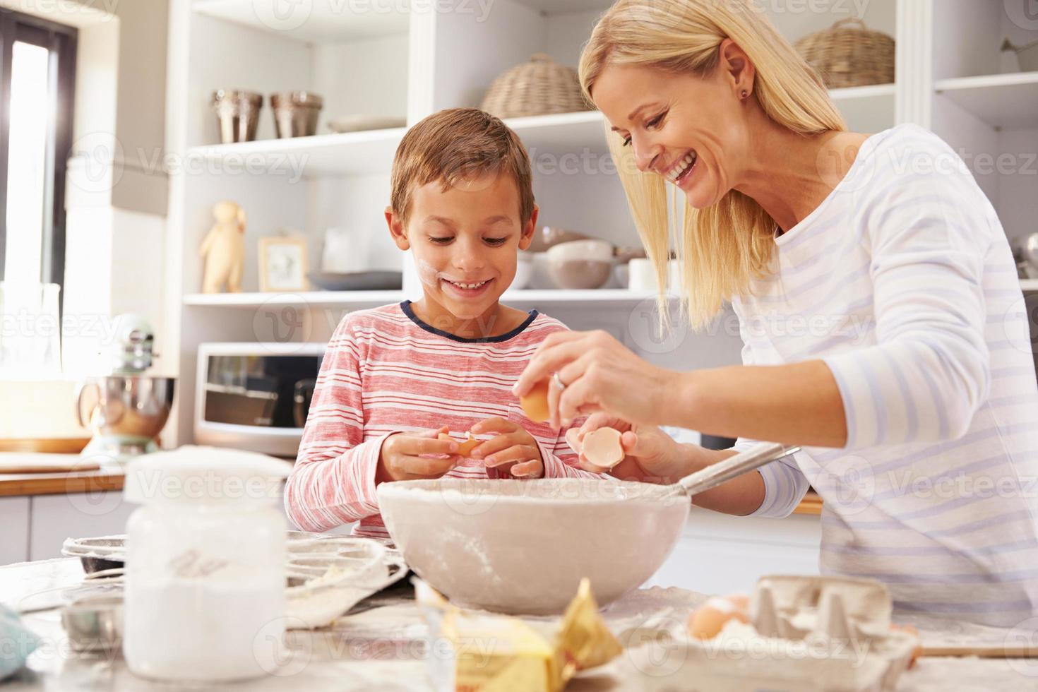 mãe e filho juntos a cozinhar em casa foto