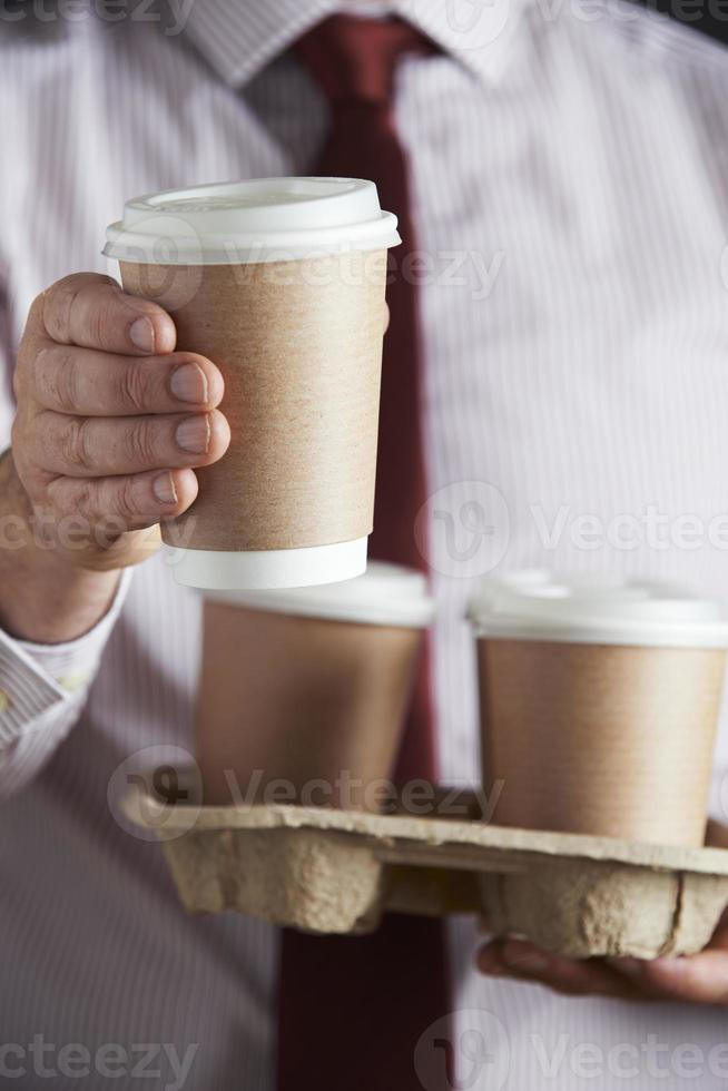 empresário, segurando a bandeja de café para viagem foto