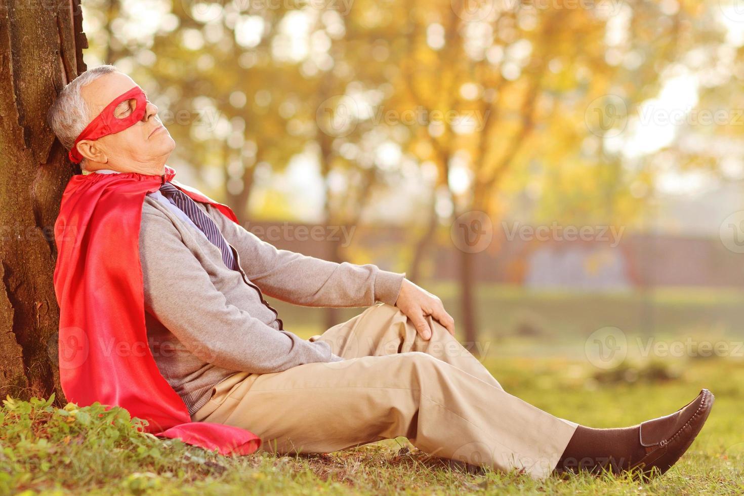 sênior em roupa de super-herói, apoiando-se na árvore foto