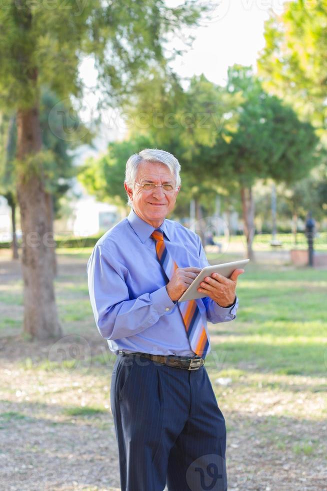 empresário trabalhando e segurando um tablet foto