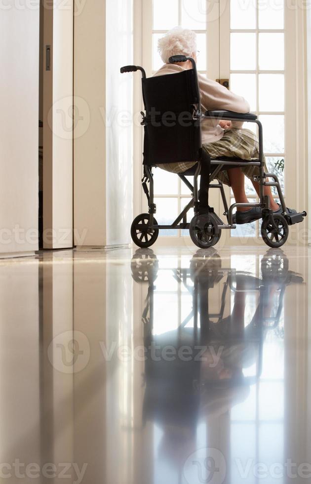 mulher sênior com deficiência, sentado na cadeira de rodas foto