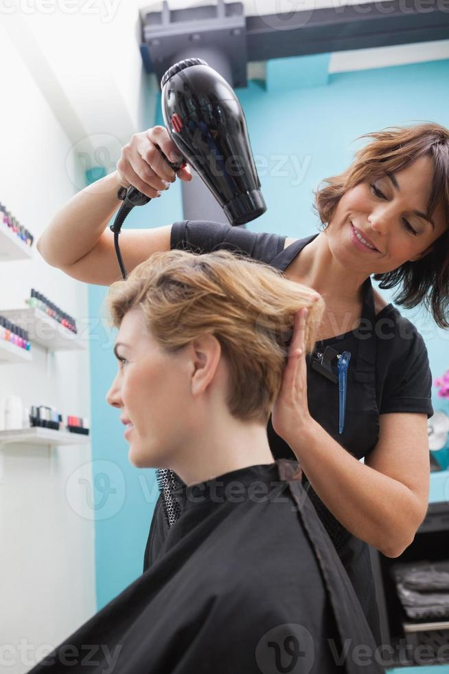 cabeleireiro secando um cabelo de clientes foto