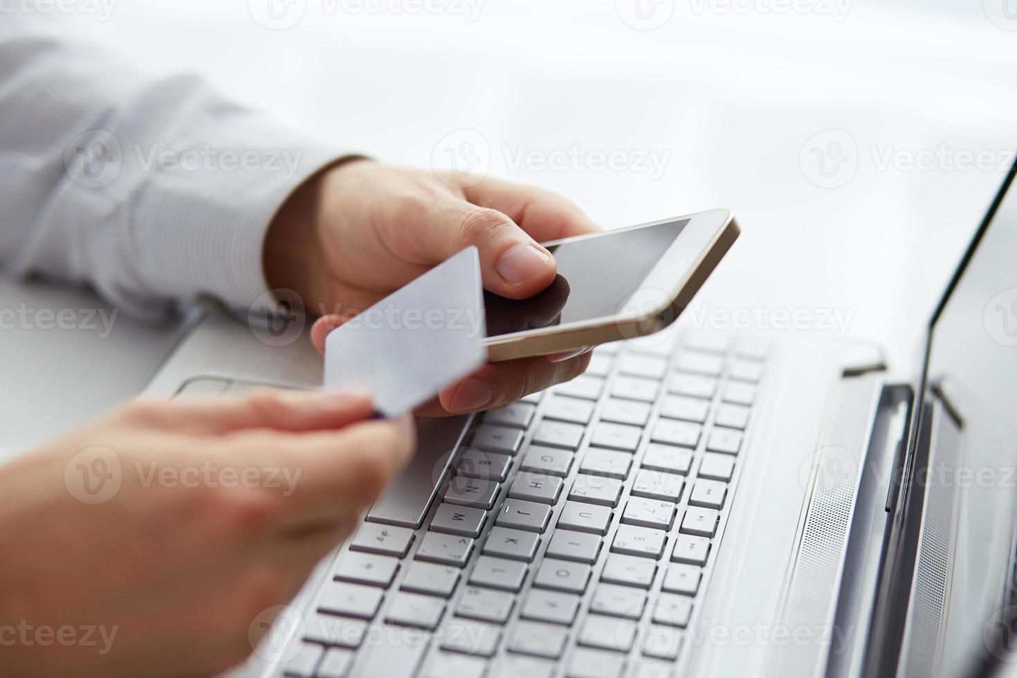homem com telefone celular e pagamento com cartão de crédito foto