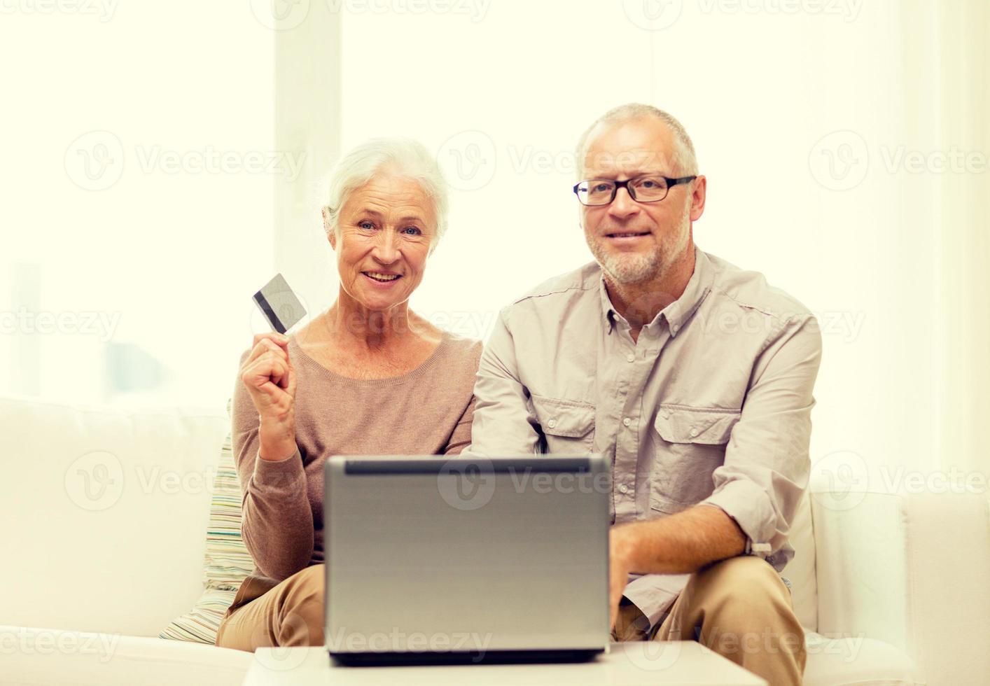 feliz casal sênior com laptop e cartão de crédito foto