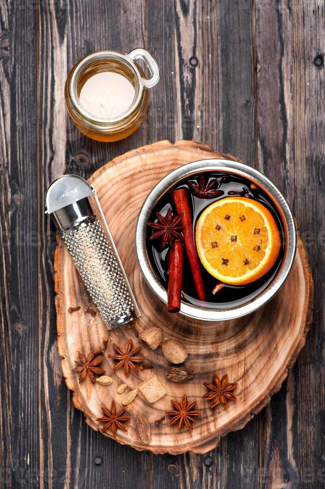 bebida quente de Natal mulled vinho com especiarias sobre madeira foto