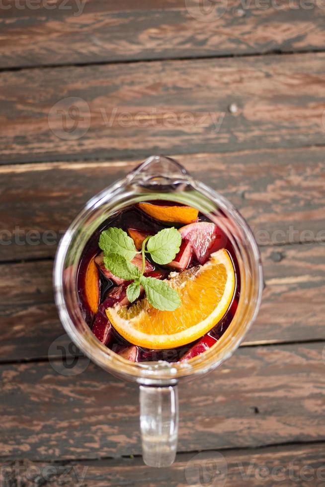 sangria de laranja e maçã em um fundo de madeira foto