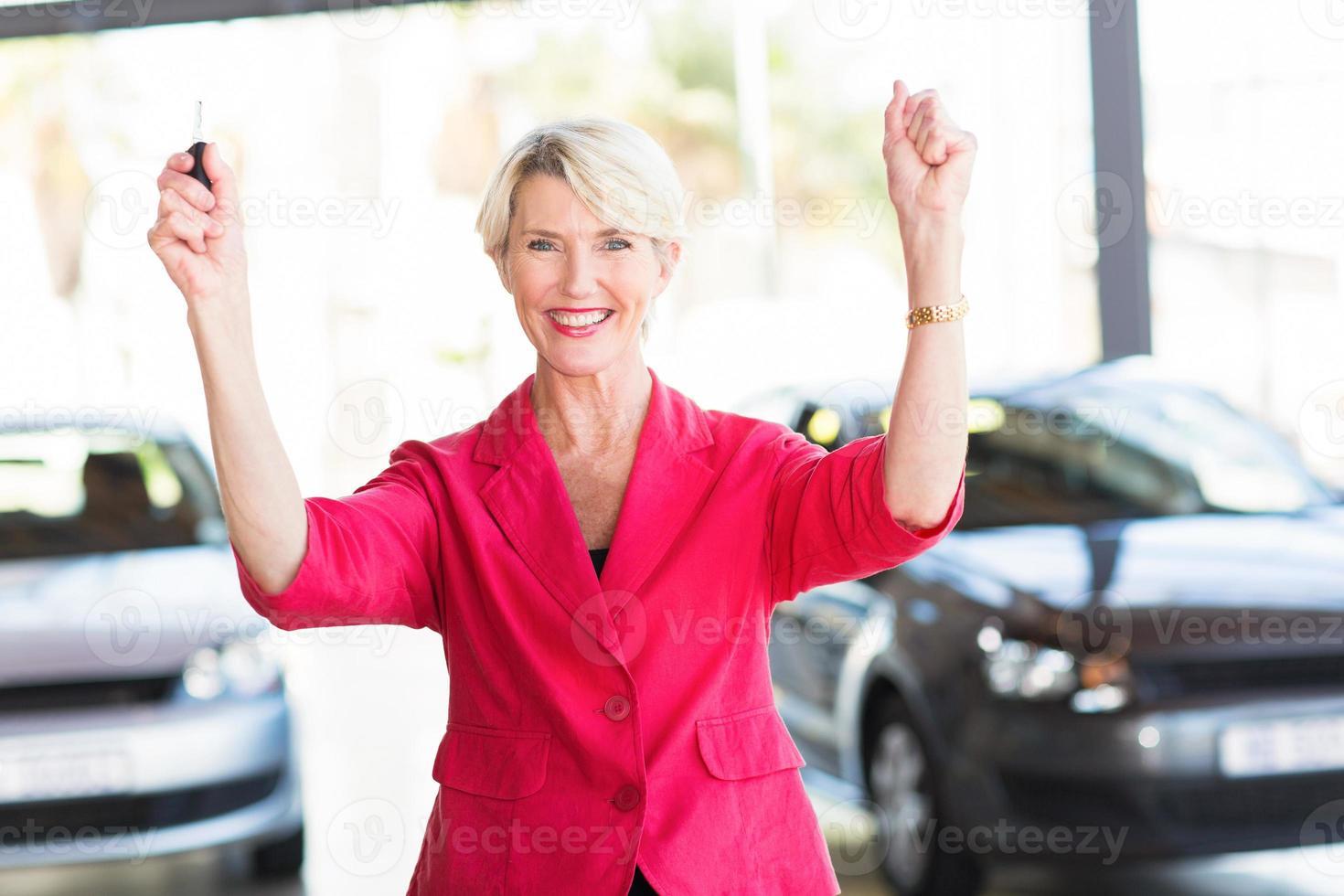 mulher sênior, coletando seu carro novo da concessionária foto