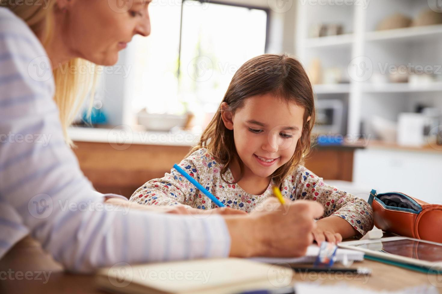 mãe ensinando sua filha em casa foto