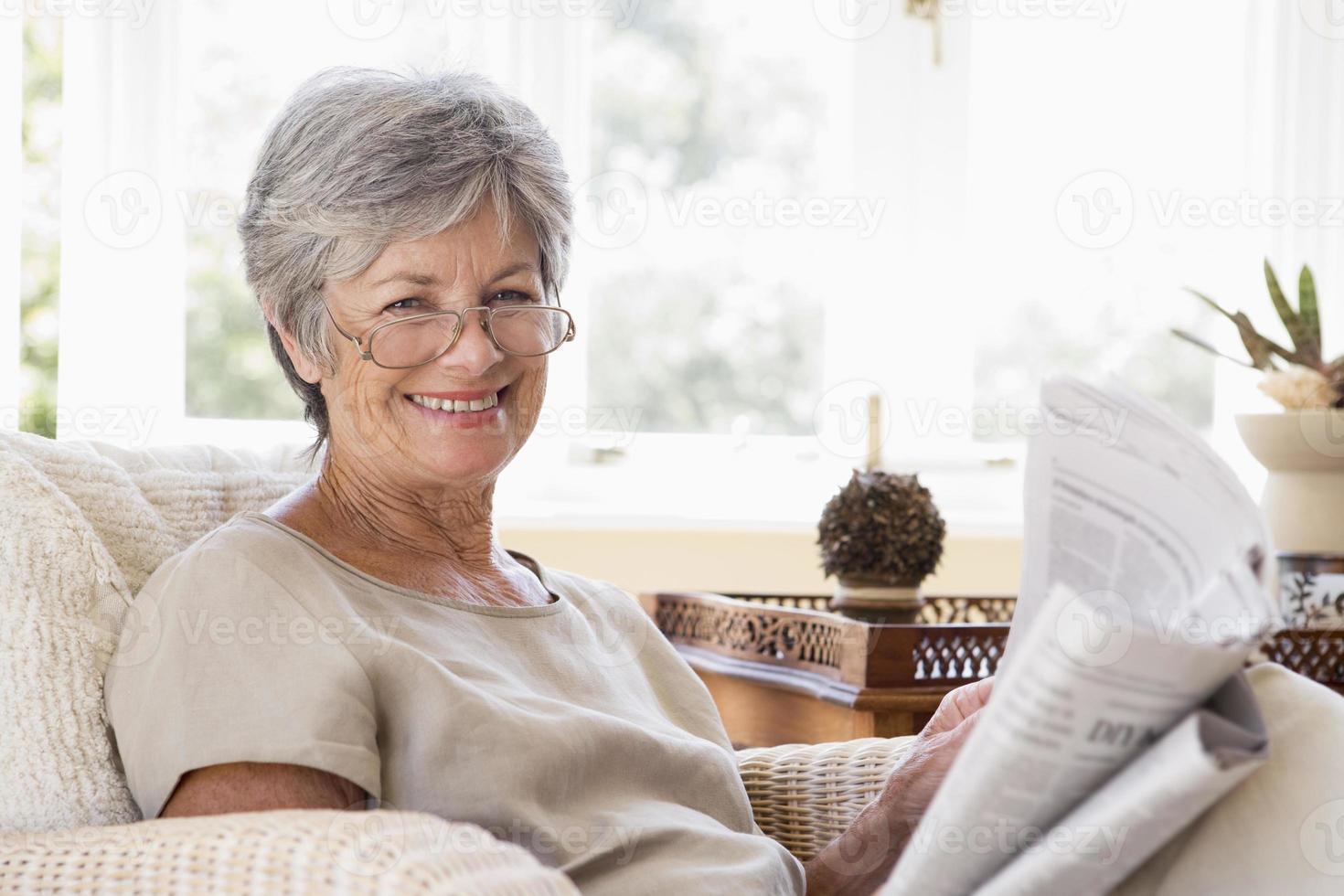 mulher na sala lendo jornal sorrindo foto