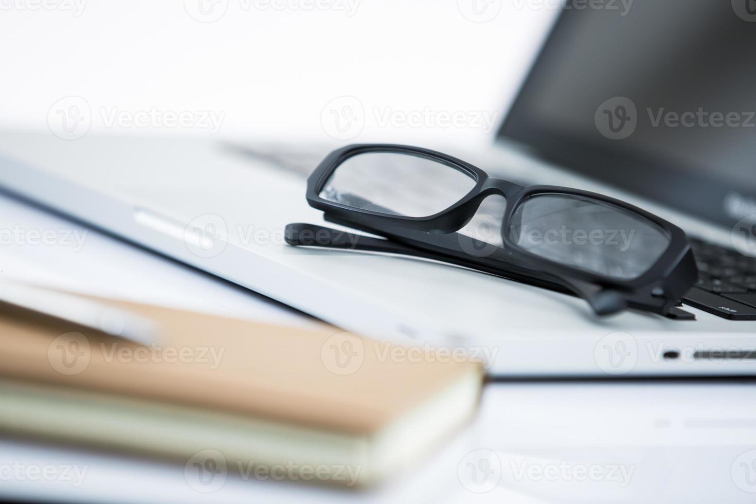 local de trabalho de escritório com laptop e caneta foto