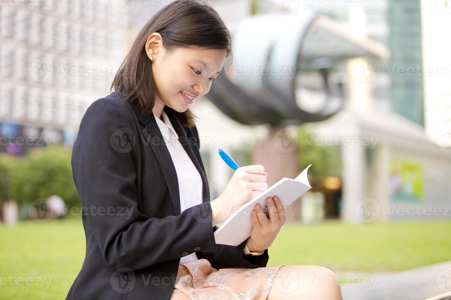 executivo de negócios asiáticos feminino jovem, escrevendo no bloco de notas foto