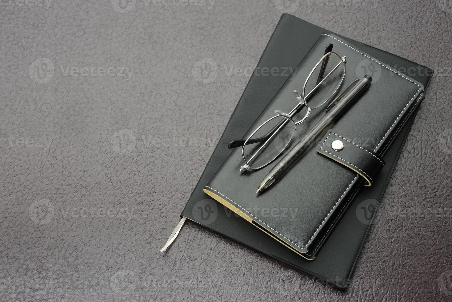 itens de negócios, óculos, caneta e organizador pessoal foto