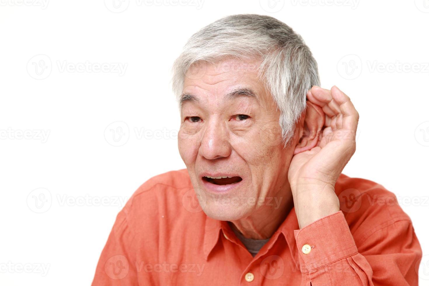 homem japonês sênior com a mão atrás da orelha, ouvindo atentamente foto