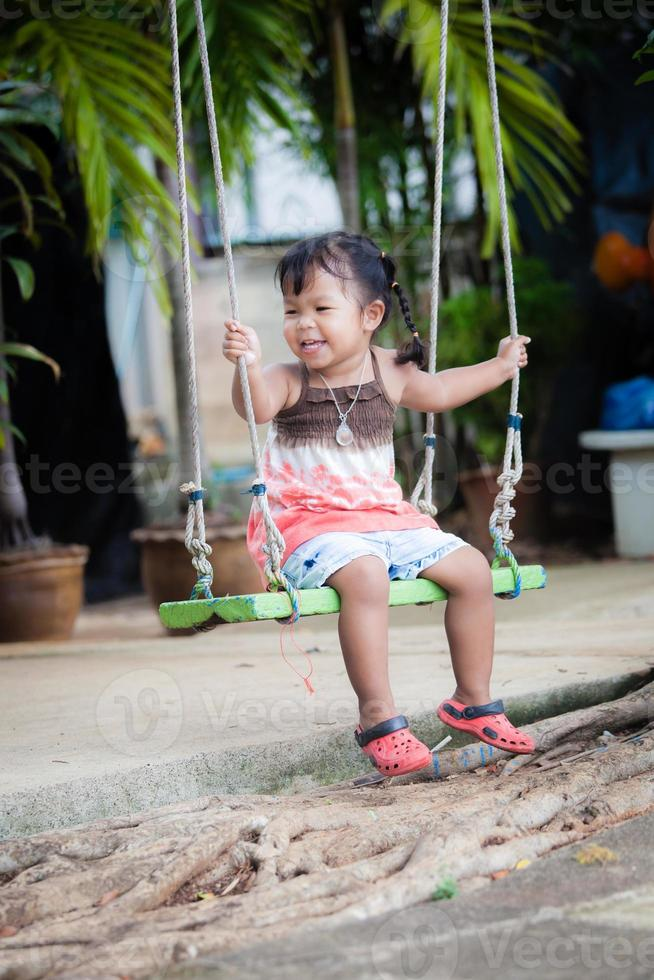 menina jogar balanço no jardim foto