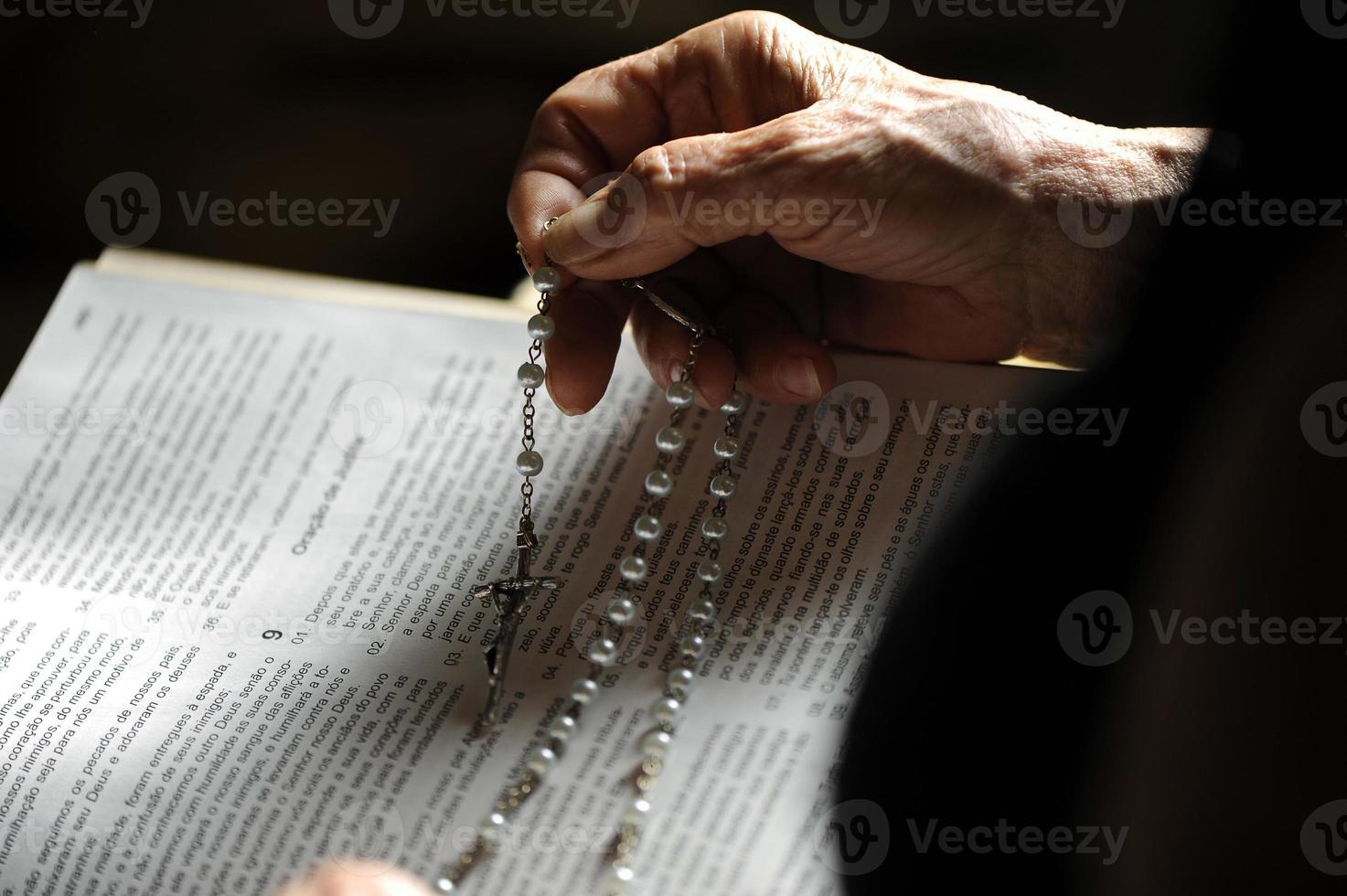 mãos do idoso na Bíblia velha foto