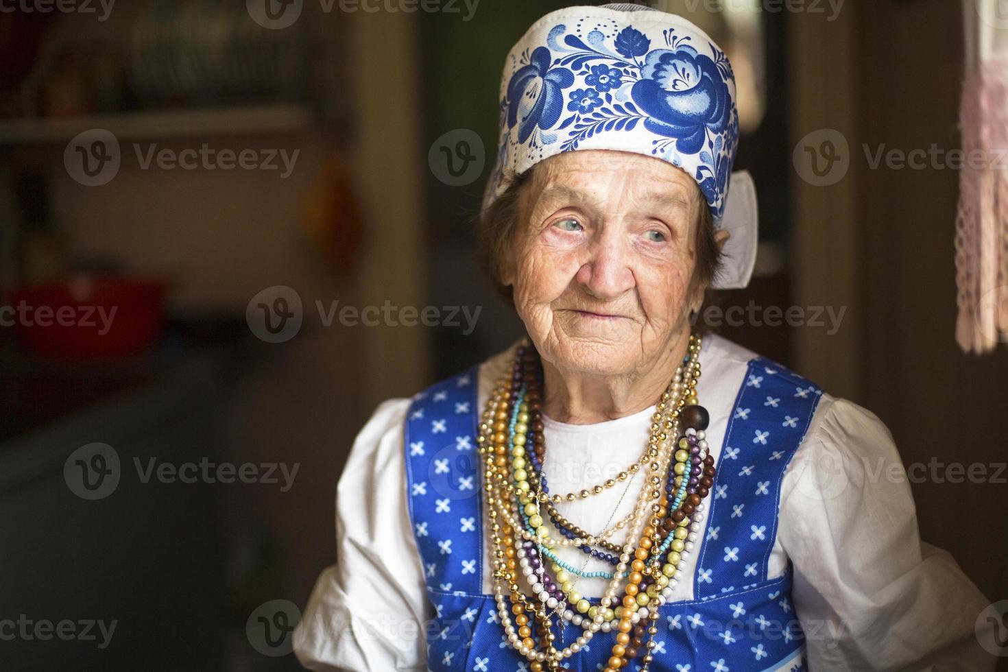 velha em roupas étnicas em sua casa. foto