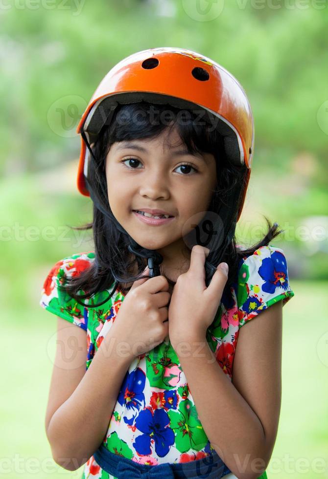 crianças asiáticas usando capacete no parque verde foto