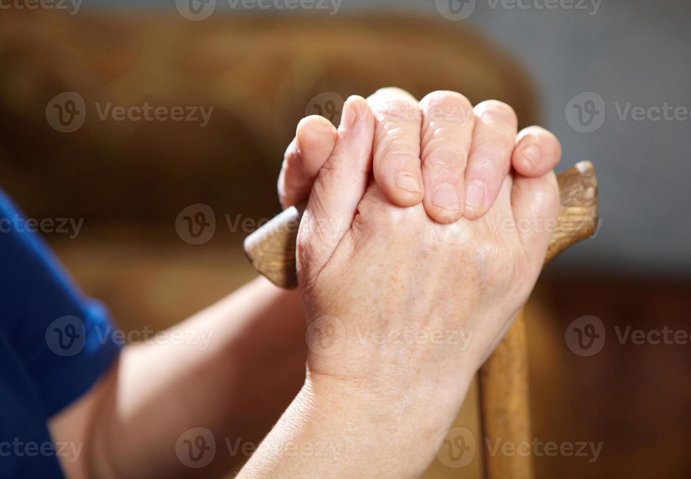 mãos de mulher velha com bengala foto