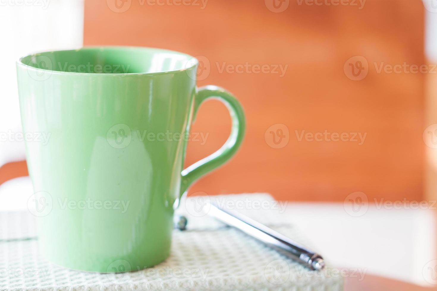 caneca verde closeup com caneta e caderno foto