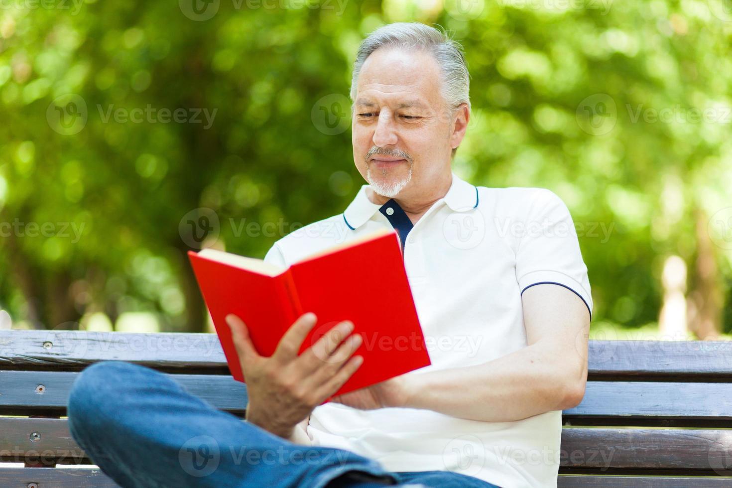 homem maduro, lendo um livro foto
