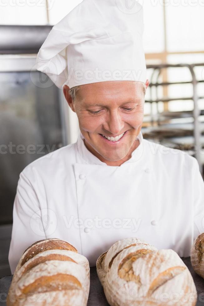 padeiro feliz mostrando a bandeja de pão fresco foto