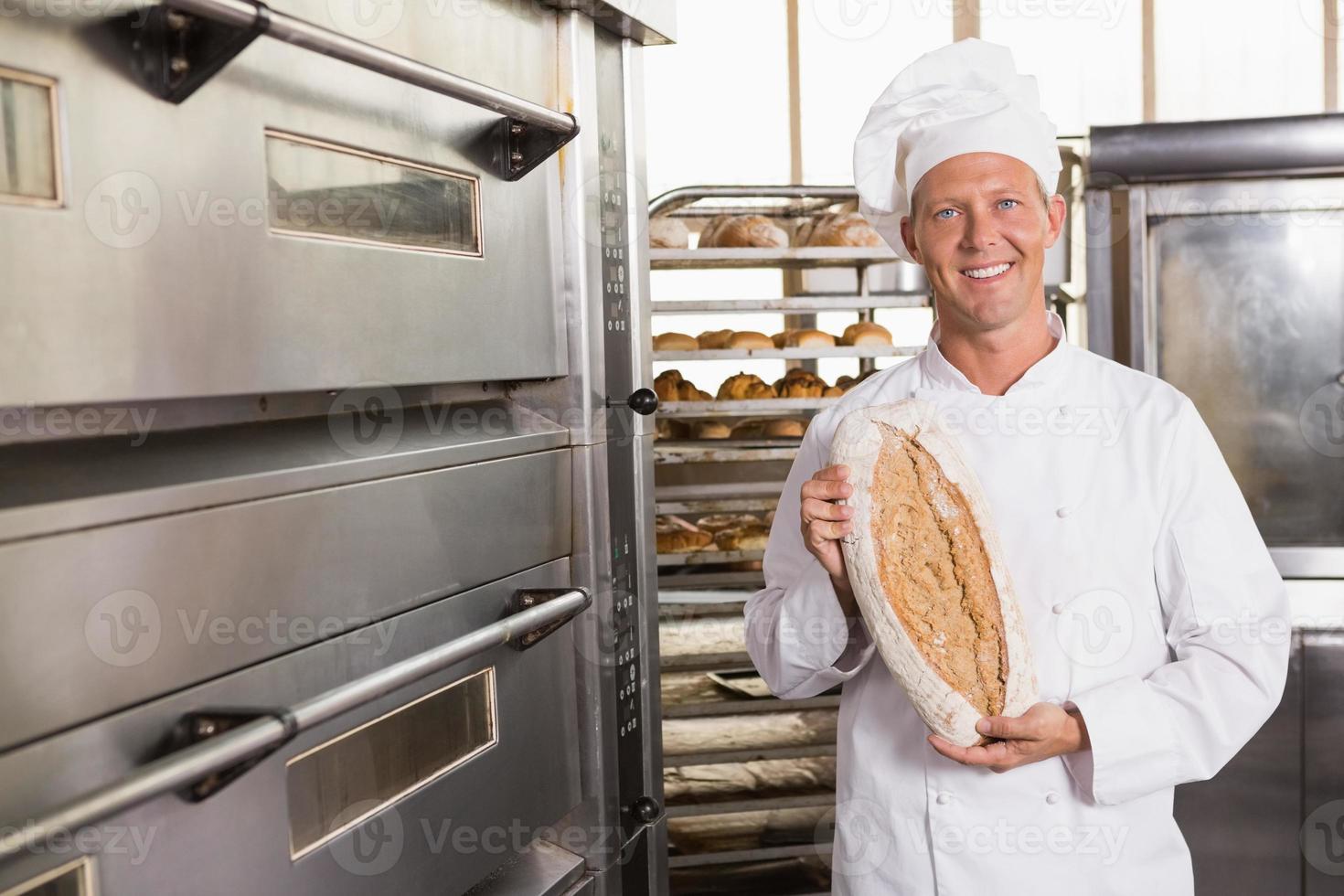 padeiro mostrando pão fresco foto