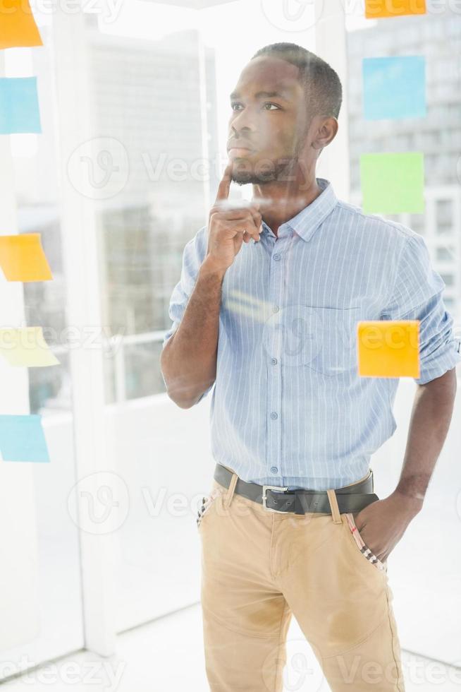 empresário pensativo olhando notas auto-adesivas na janela foto