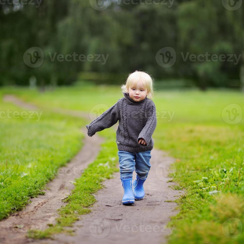 criança andando no dia de outono foto