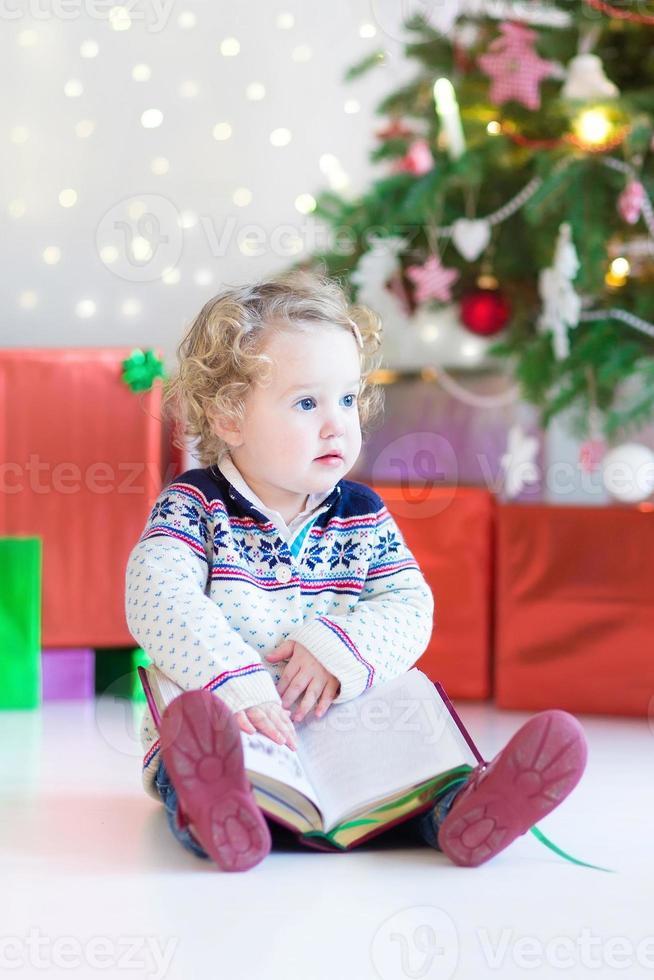 linda menina criança lendo livro sob a árvore de Natal decorada foto