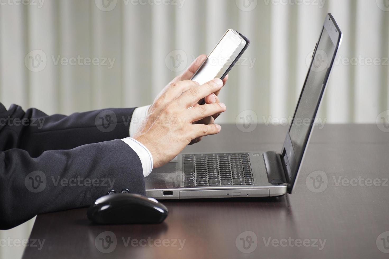 homem de negócios usando telefone inteligente no escritório foto