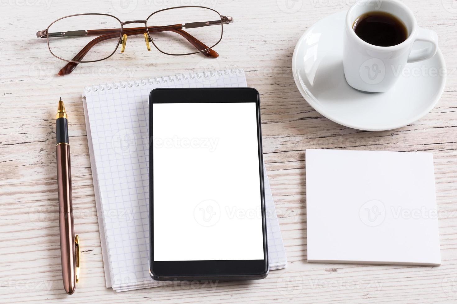 notebook com óculos, lápis, telefone inteligente e xícara de café foto