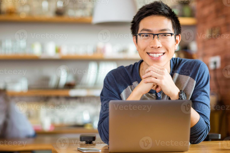 homem asiático positivo em copos com laptop foto