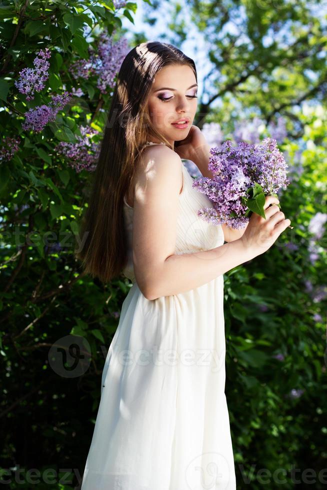menina bonita com uma flores lilás foto