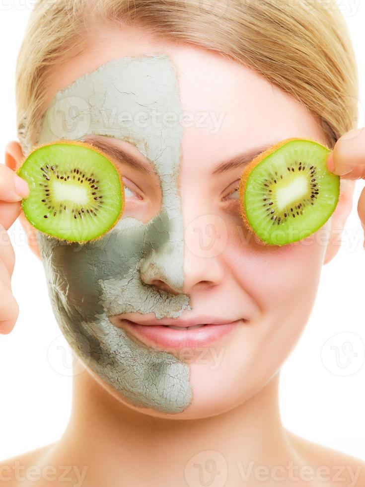 mulher com máscara facial de argila cobrindo os olhos com kiwi foto