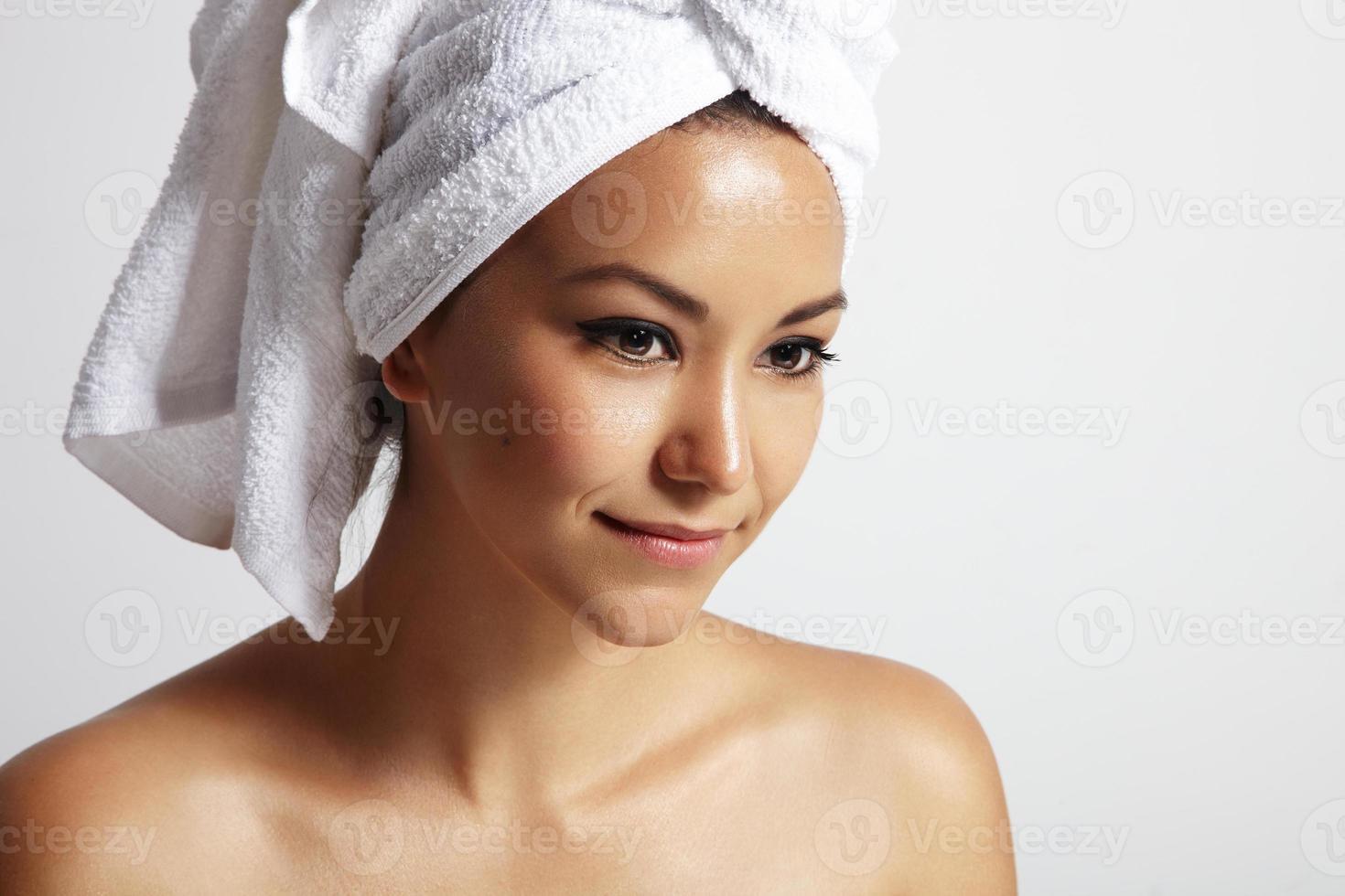 mulher de beleza com uma toalha branca na cabeça foto